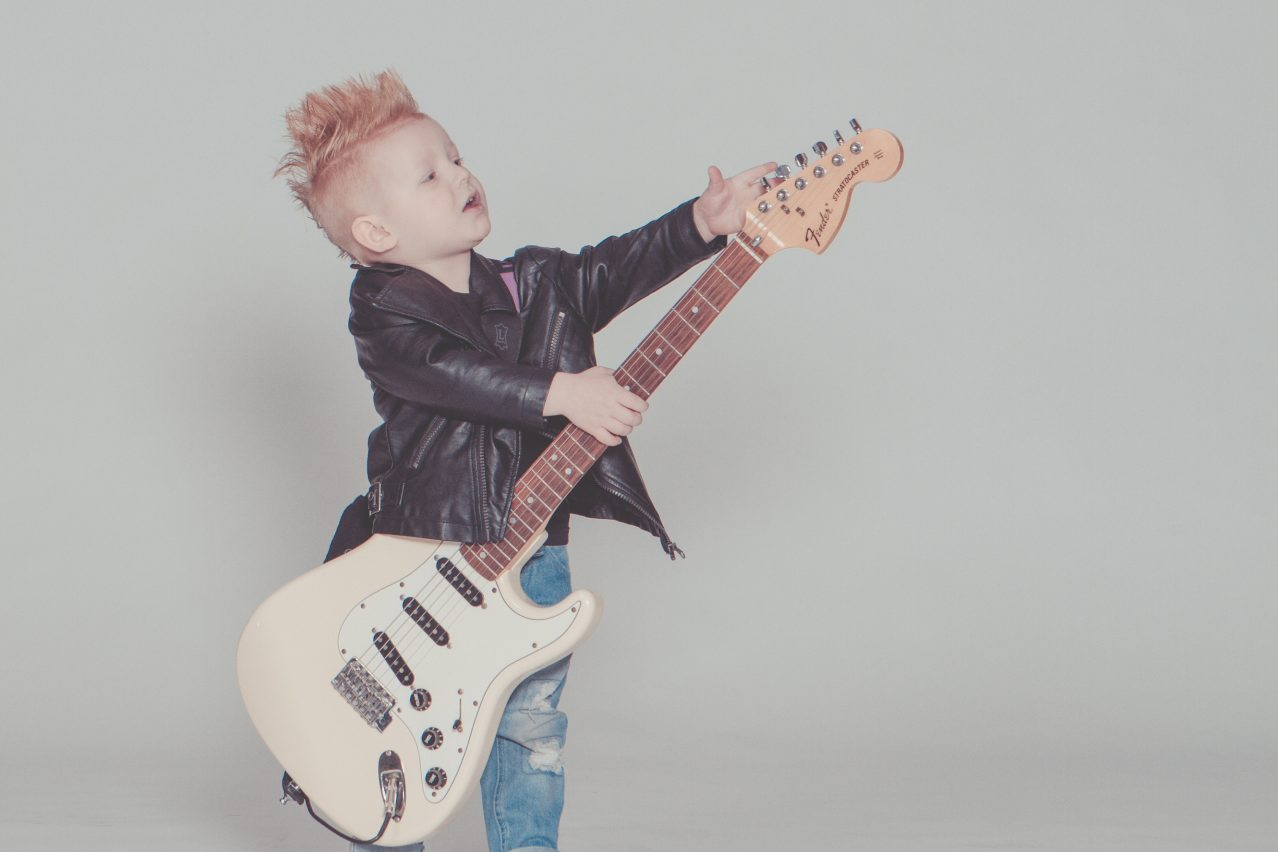 a kid playing a guitar